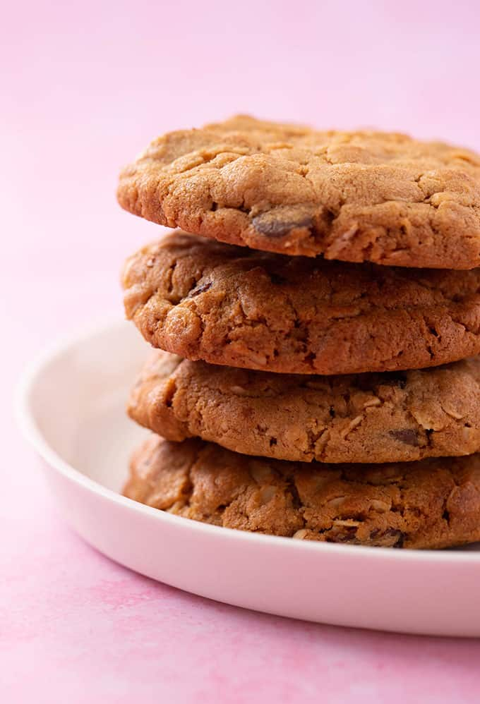 A close up shot of a stack of Peanut Butter Oatmeal Cookies with a light pink background