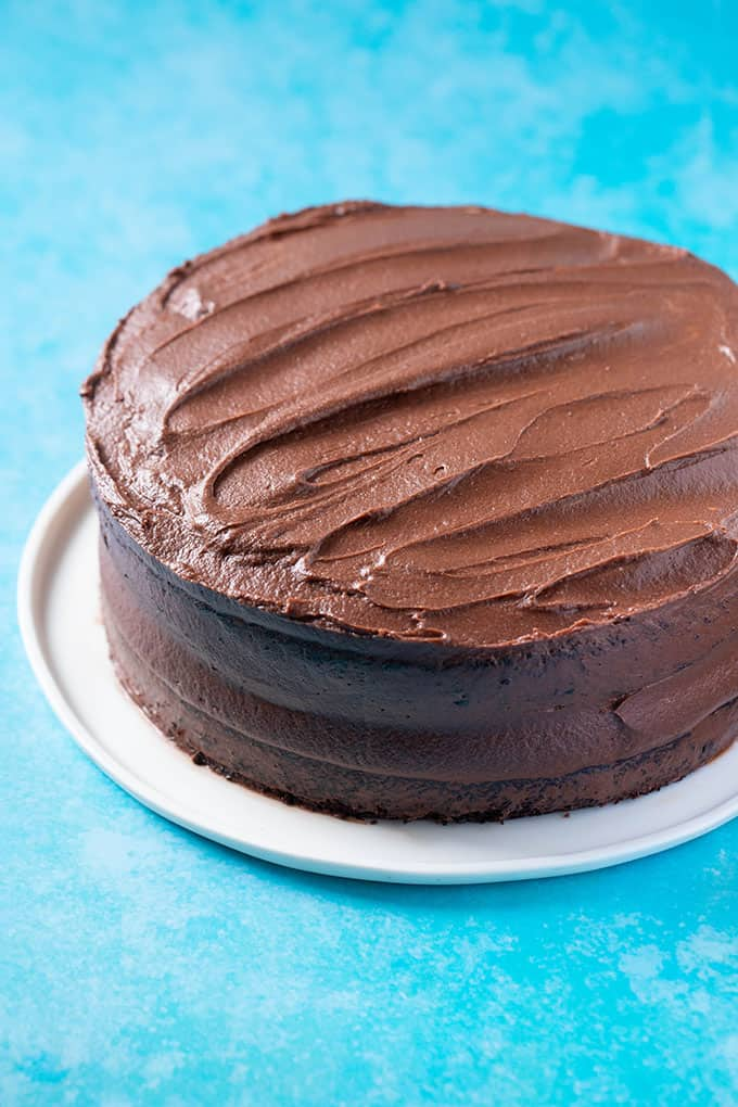 A Vegan Chocolate Cake covered in chocolate frosting on a white cake plate