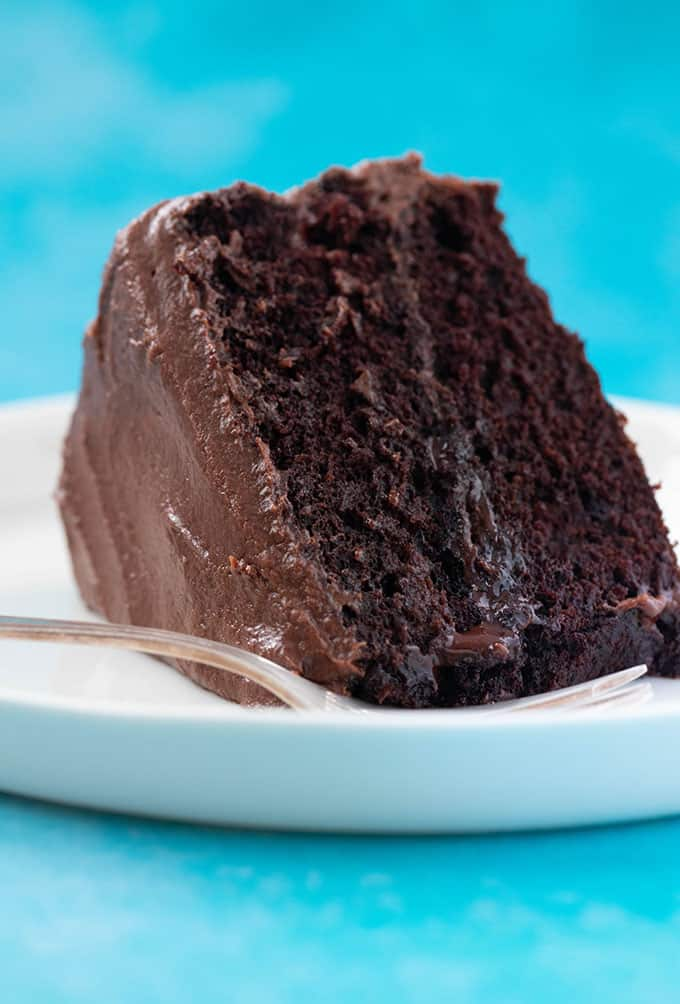 A big slice of Vegan Chocolate Cake on a white plate
