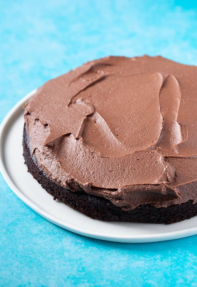 A chocolate cake covered in vegan chocolate frosting