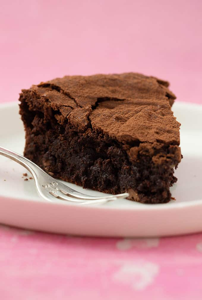 A gooey piece of Brownie Cake on a cake plate with a cake fork