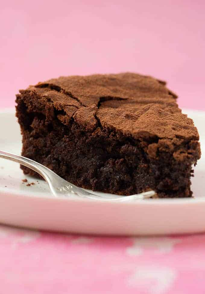 A slice of Brownie Cake on a pink background