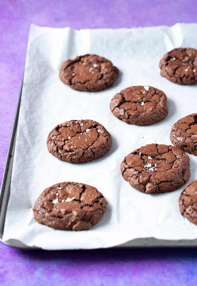 An oven tray with freshly baked Brownie Cookies sprinkled with sea salt