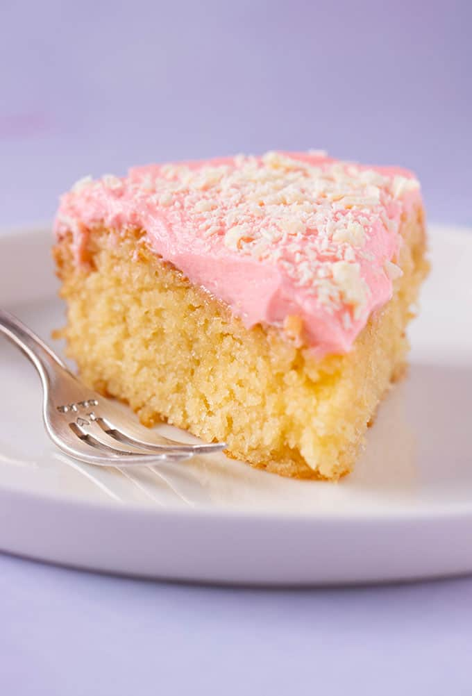 Close up of a slice of Butter Cake with pink frosting on a cake plate