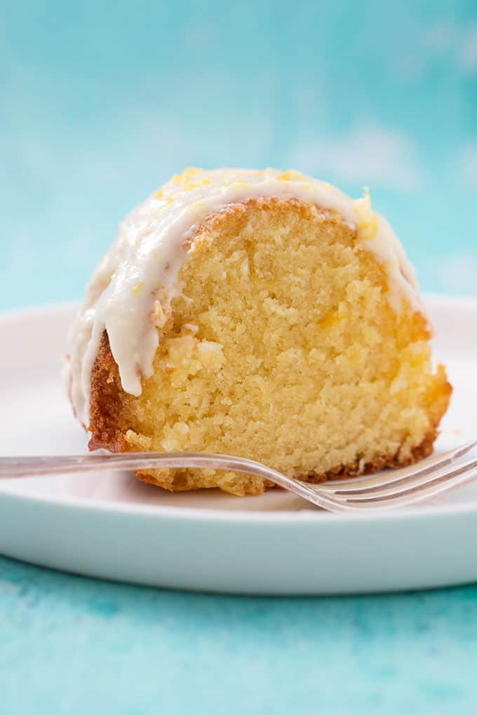 A piece of Lemon Bundt Cake on a white cake plate