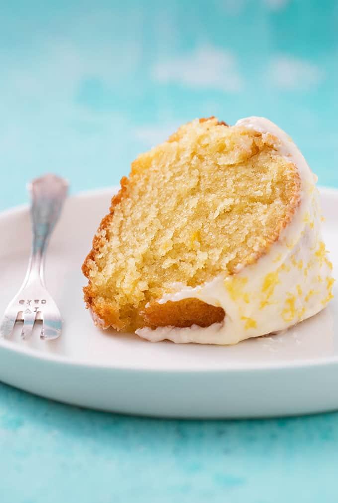A slice of homemade Lemon Bundt Cake on a white plate