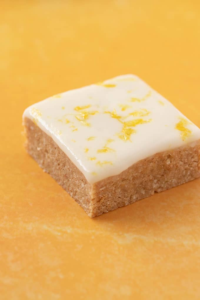 A large piece of Lemon Coconut Slice decorated with fresh lemon zest