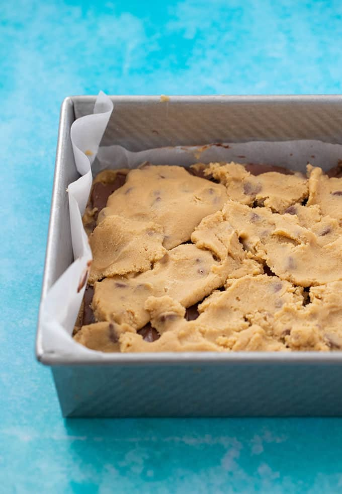 A baking tray filled with cookie dough and Nutella on a blue background
