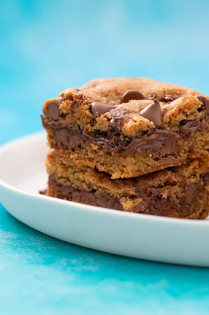 A stack of homemade Nutella Stuffed Chocolate Chip Cookie Bars on a white plate