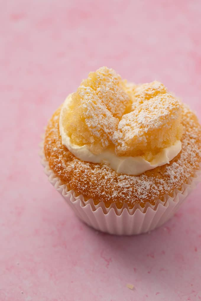Close up view of a homemade Butterfly Cupcake dusted with icing sugar on a pink background
