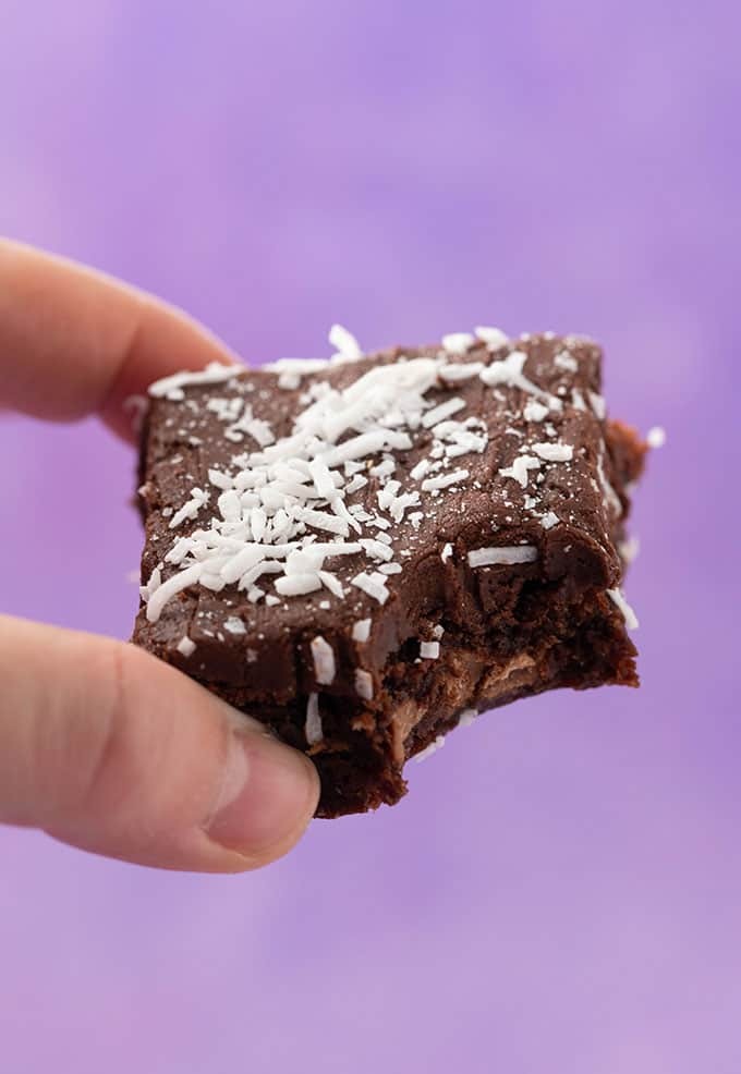 A hand holding a piece of Chocolate Coconut Slice on a purple background