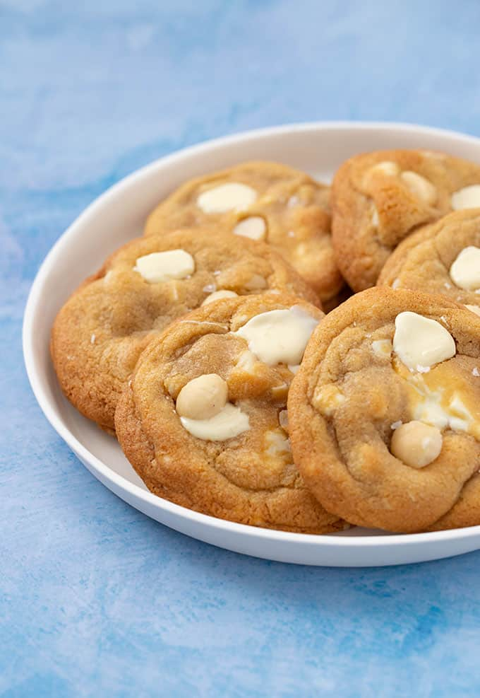 Golden white chocolate and macadamia cookies on a white plate