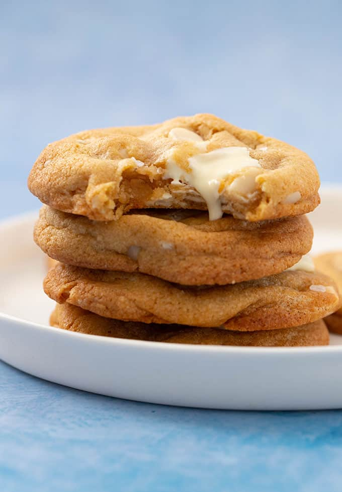 A stack of homemade Macadamia Cookies with white chocolate dripping down the side