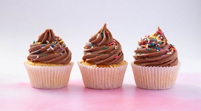 Three cupcakes decorated with swirls of chocolate frosting