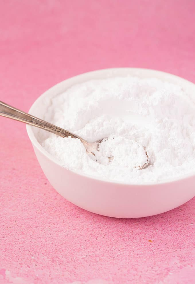 A bowl of sifted icing sugar on a pink background