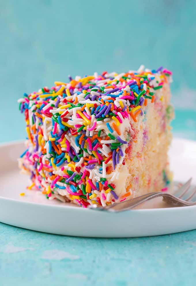 A slice of Funfetti Cake covered in colourful sprinkles