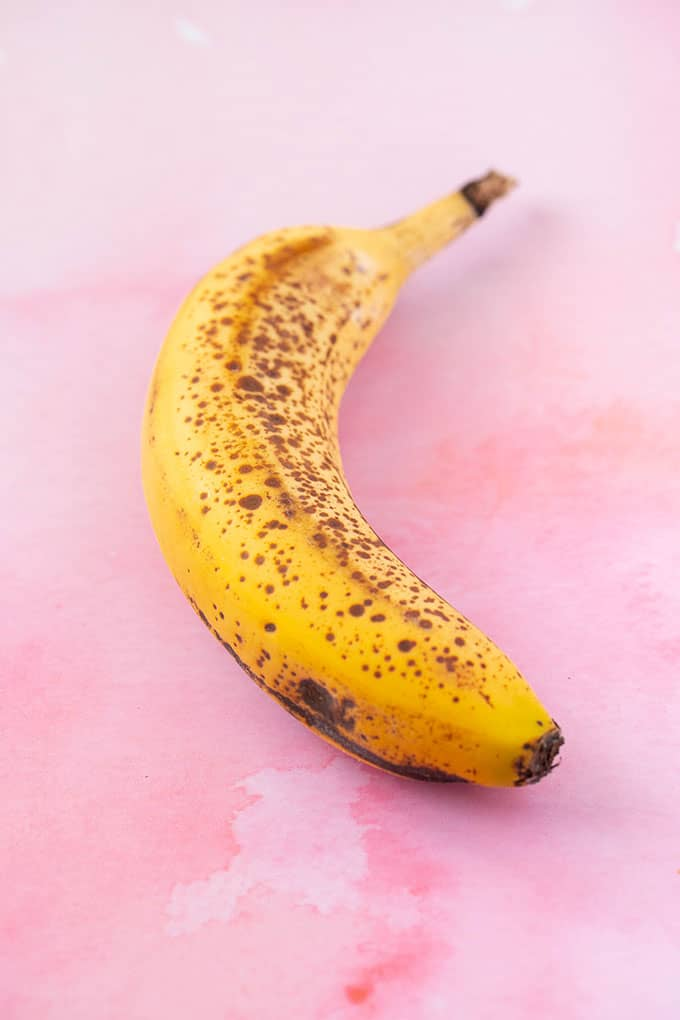 A spotty banana on a pink background