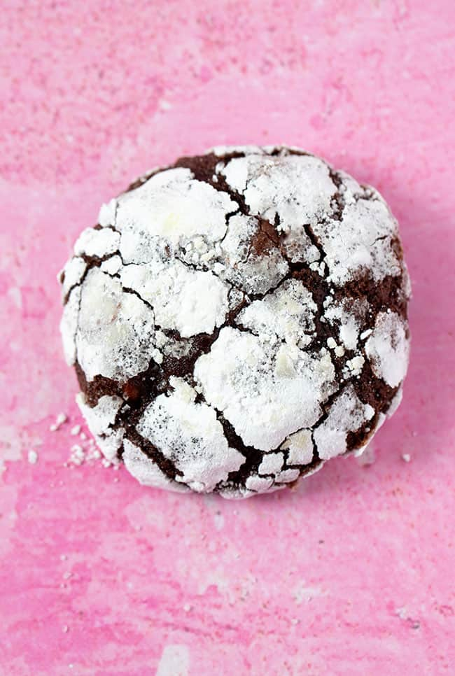 Close up of a Chocolate Crinkle Cookie on a pink background