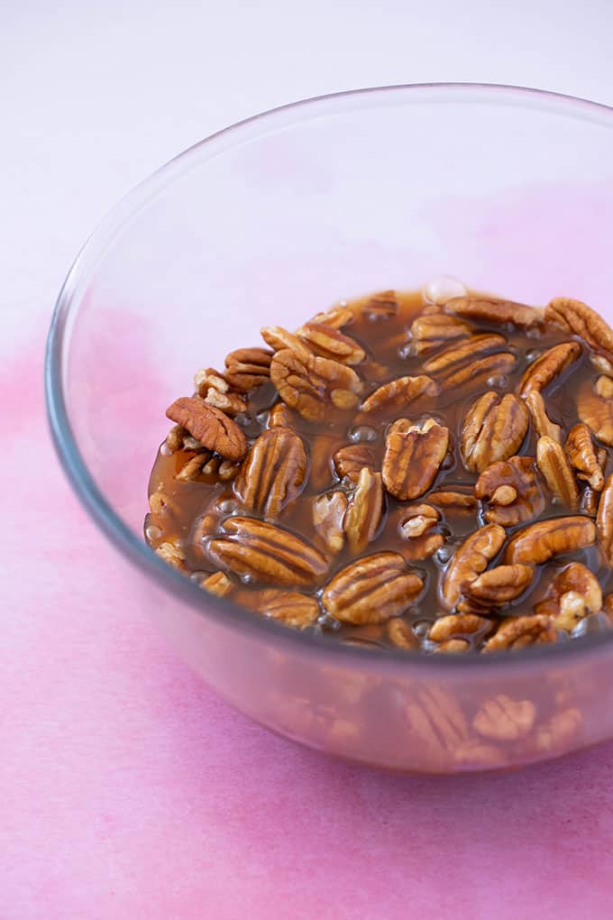 A bowl of caramel covered pecans