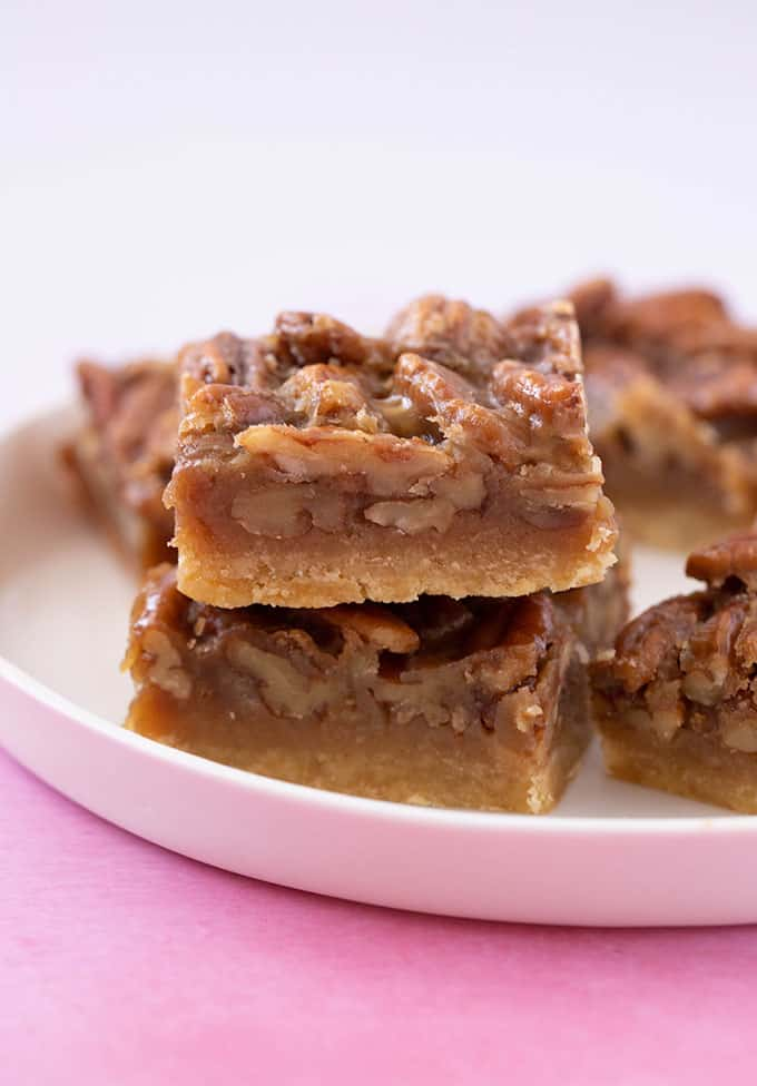 A stack of homemade Pecan Pie Bars on a white plate