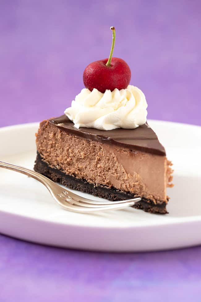 A slice of Baked Chocolate Cheesecake on a white plate