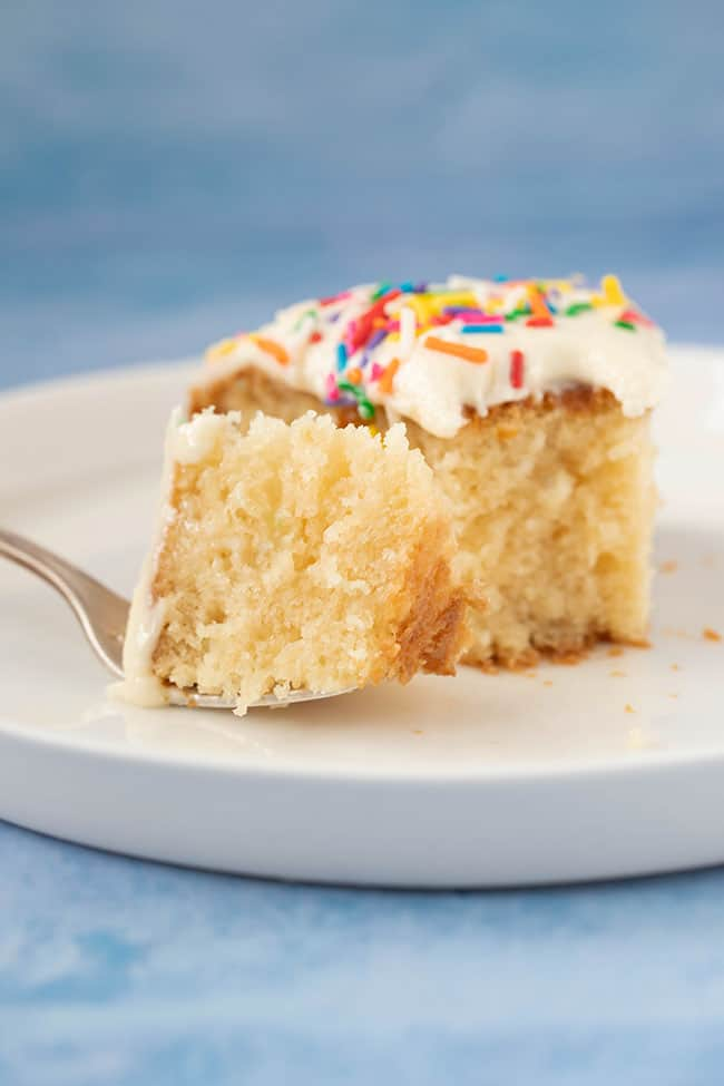 A slice of Vegan Vanilla Cake with a bite taken out of it
