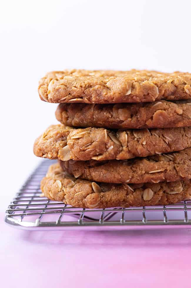 A stack of homemade Anzac Cookies sitting on a cooling rack