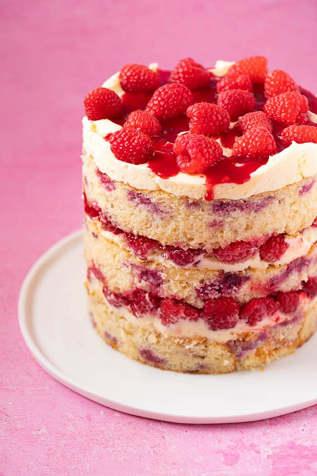 Raspberry Ripple Cake on a white plate decorated with fresh raspberries
