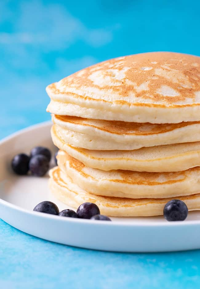 A stack of homemade Ricotta Pancakes on a blue background