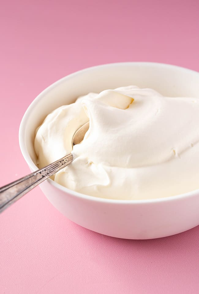 A white bowl filled with homemade whipped cream