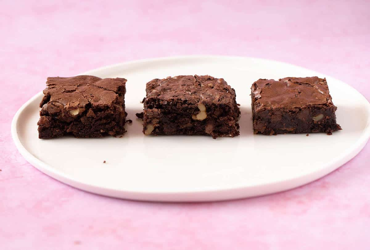 A white plate with three different brownies on a pink background