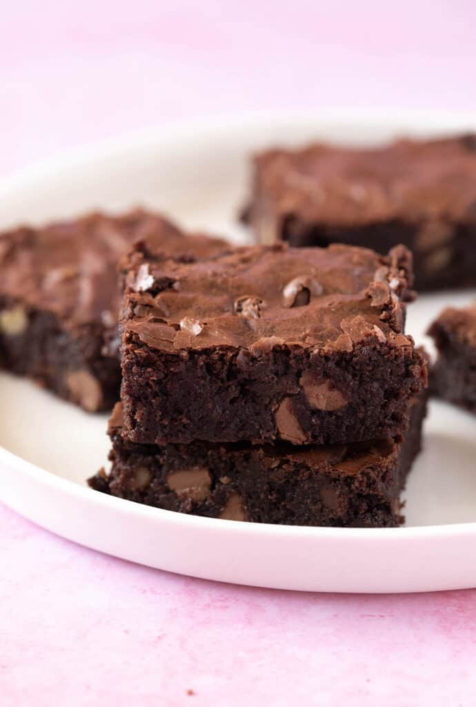 A stack of homemade Chocolate Brownies on a white plate
