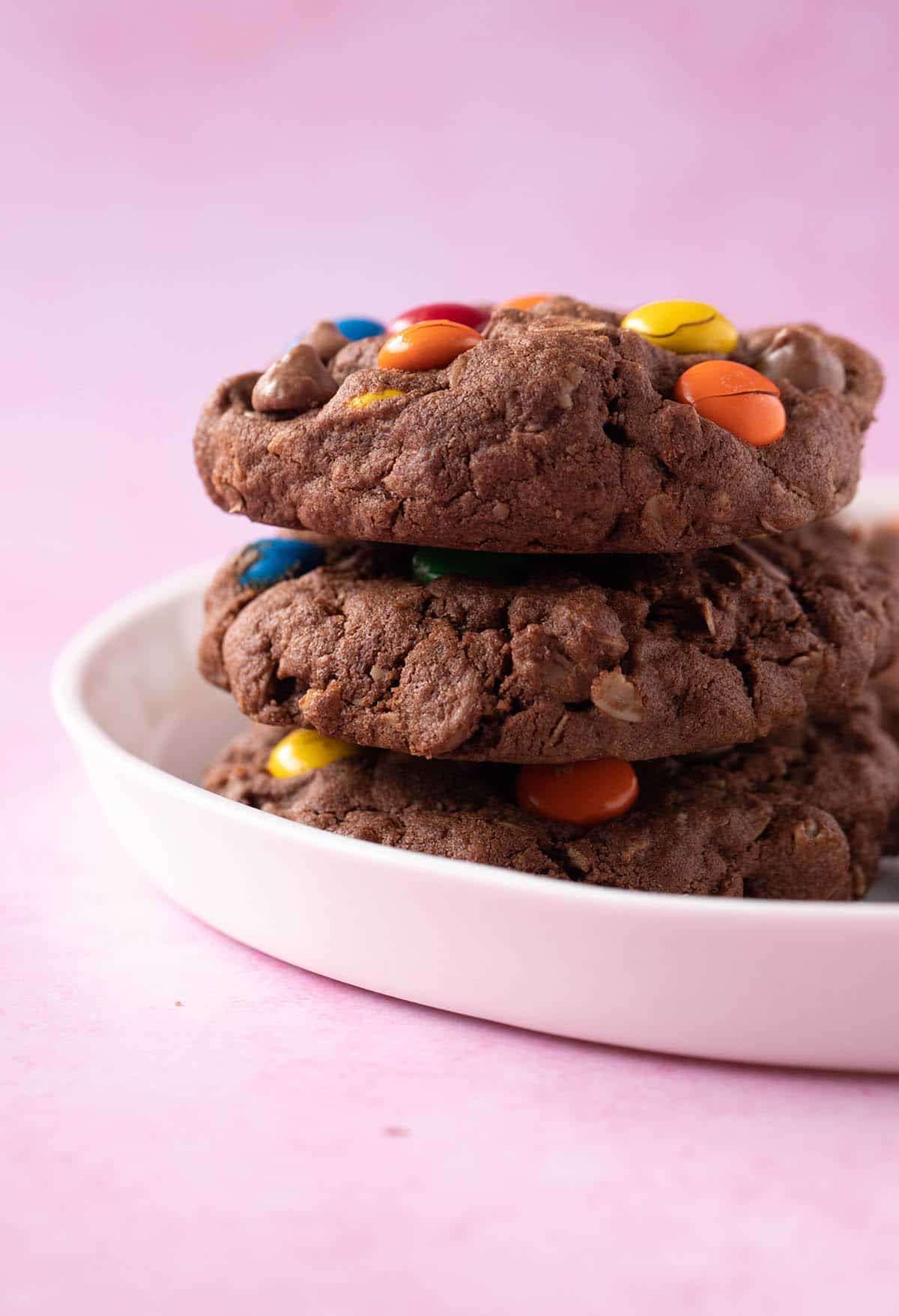 A stack of homemade Chocolate Monster Cookies on a white plate