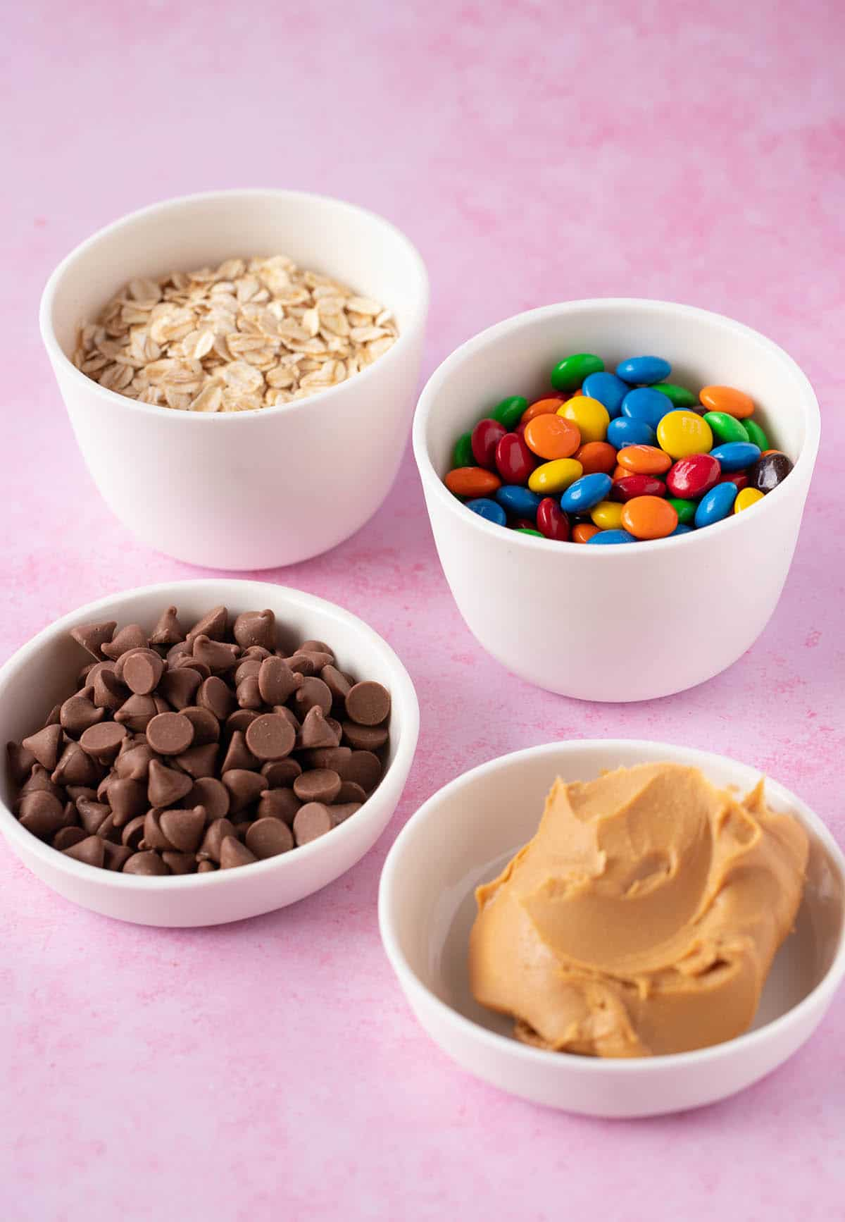 A spread of baking ingredients on a pink background including M&M's and peanut butter