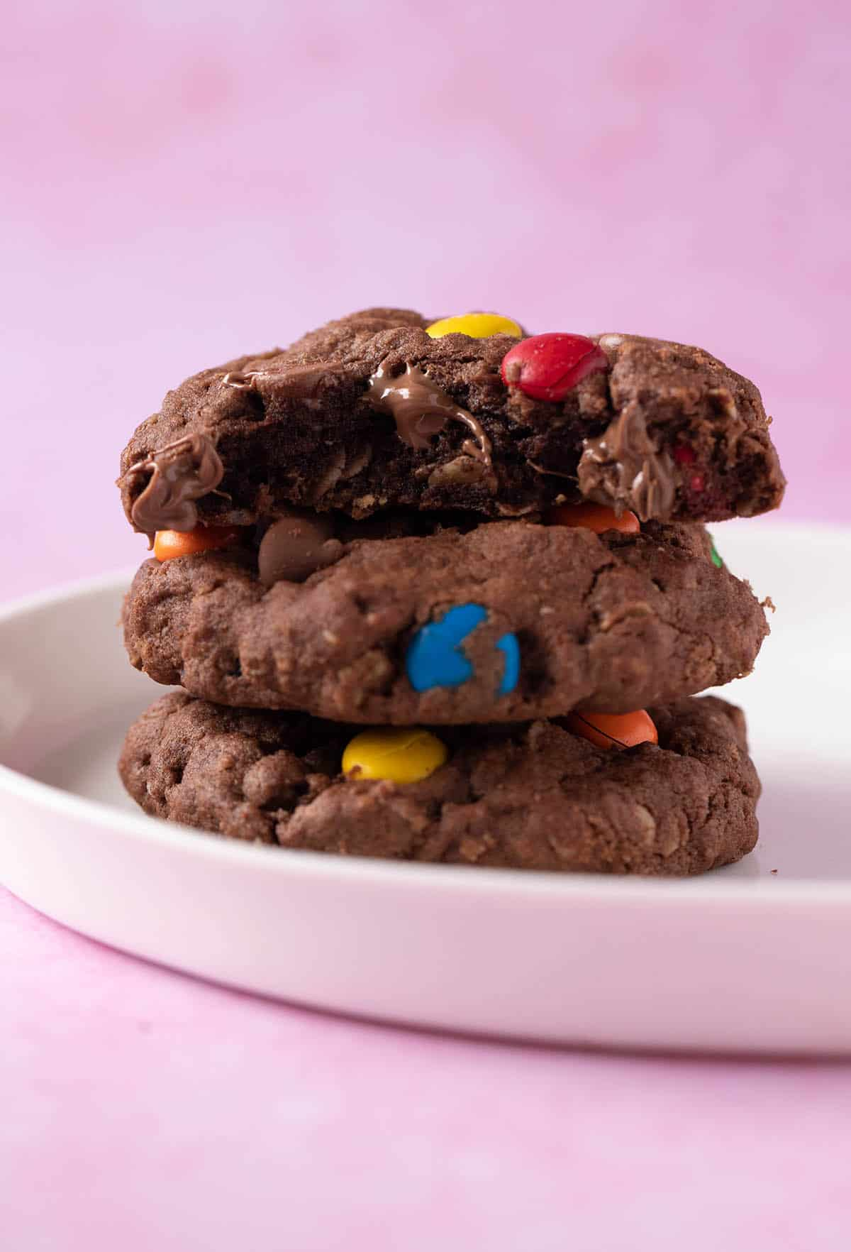 A stack of Chocolate Monster Cookies with a bite taken out of it