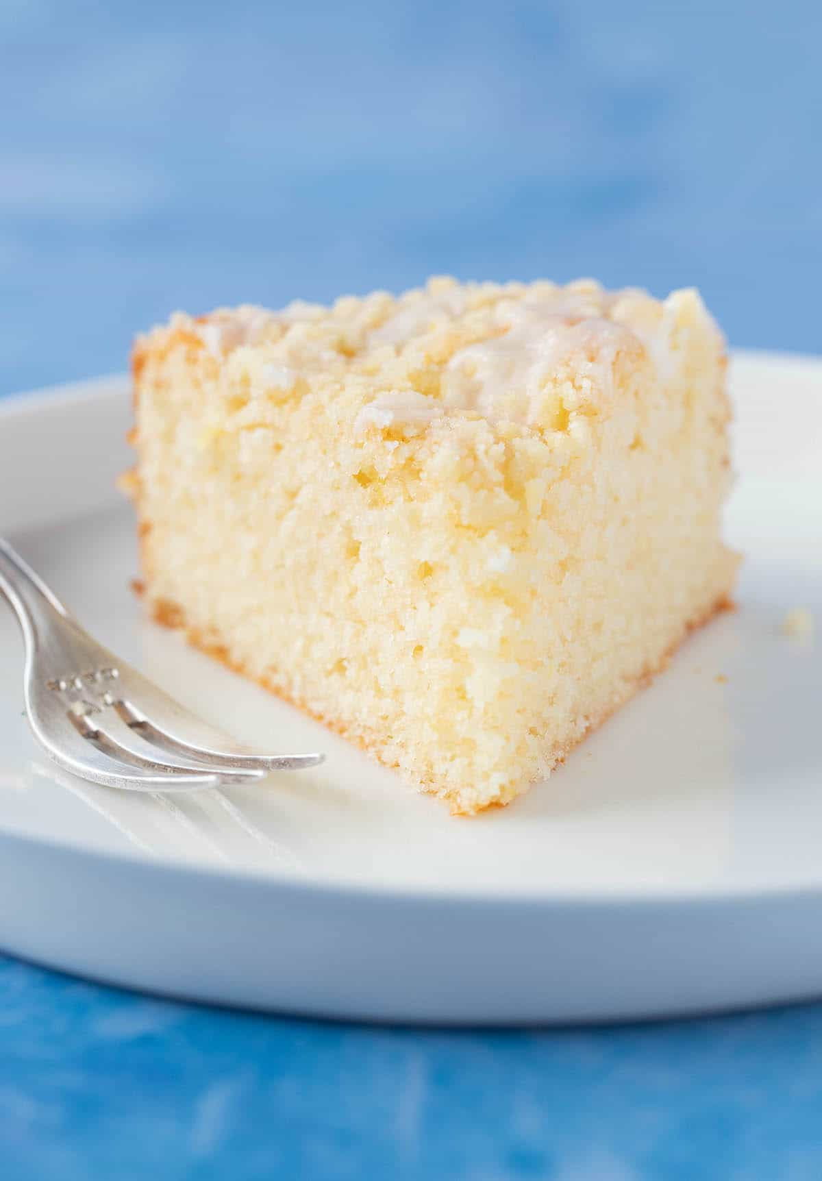 Close up of a big slice of Lemon Crumb Cake on a white plate