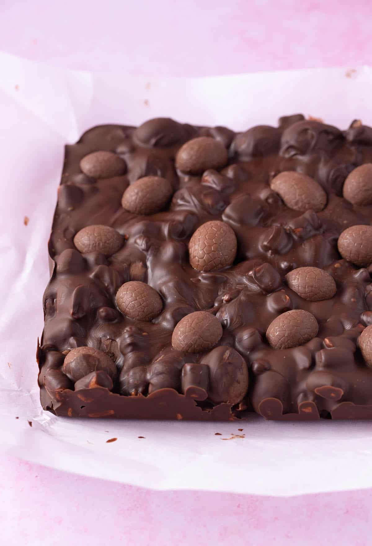 A slab of Easter Egg Rocky Road on a pink background.