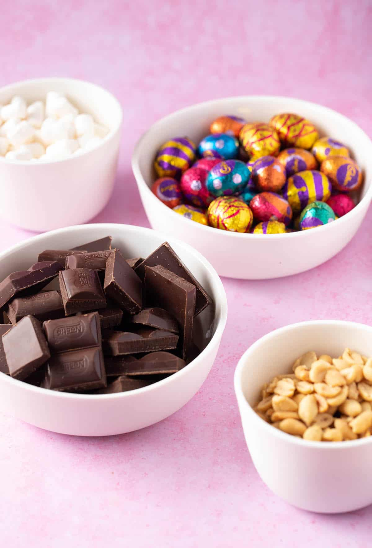 Bowls filled with chocolate, peanuts, mini marshmallows and Easter eggs