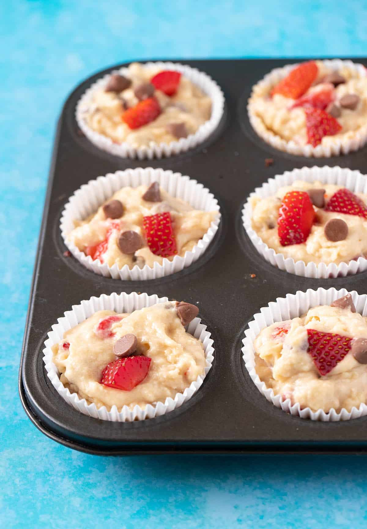 A muffin pan filled with strawberry muffin batter ready for the oven