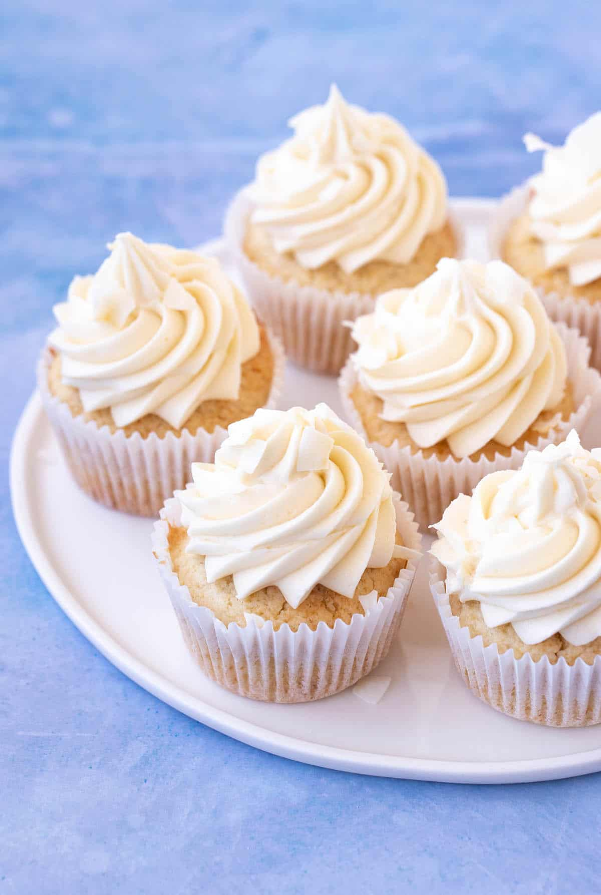 Perfect Coconut Cupcakes with swirls of creamy frosting on a blue background