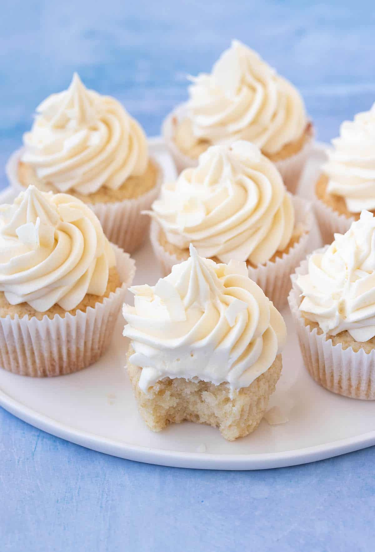 A plate filled with homemade Coconut Cupcakes. One has a bit taken out of it.