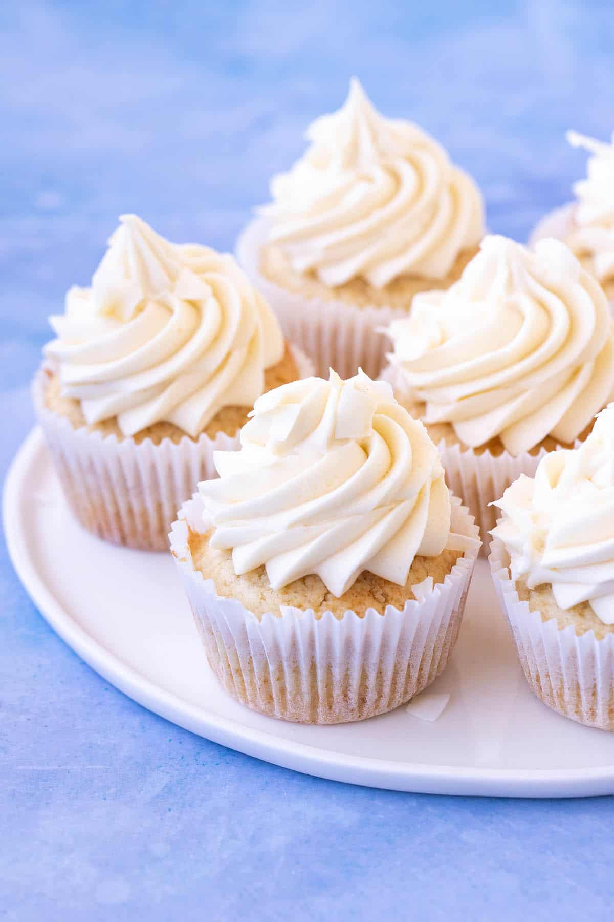 A plate of beautifully decorated Coconut Cupcakes on a white plate