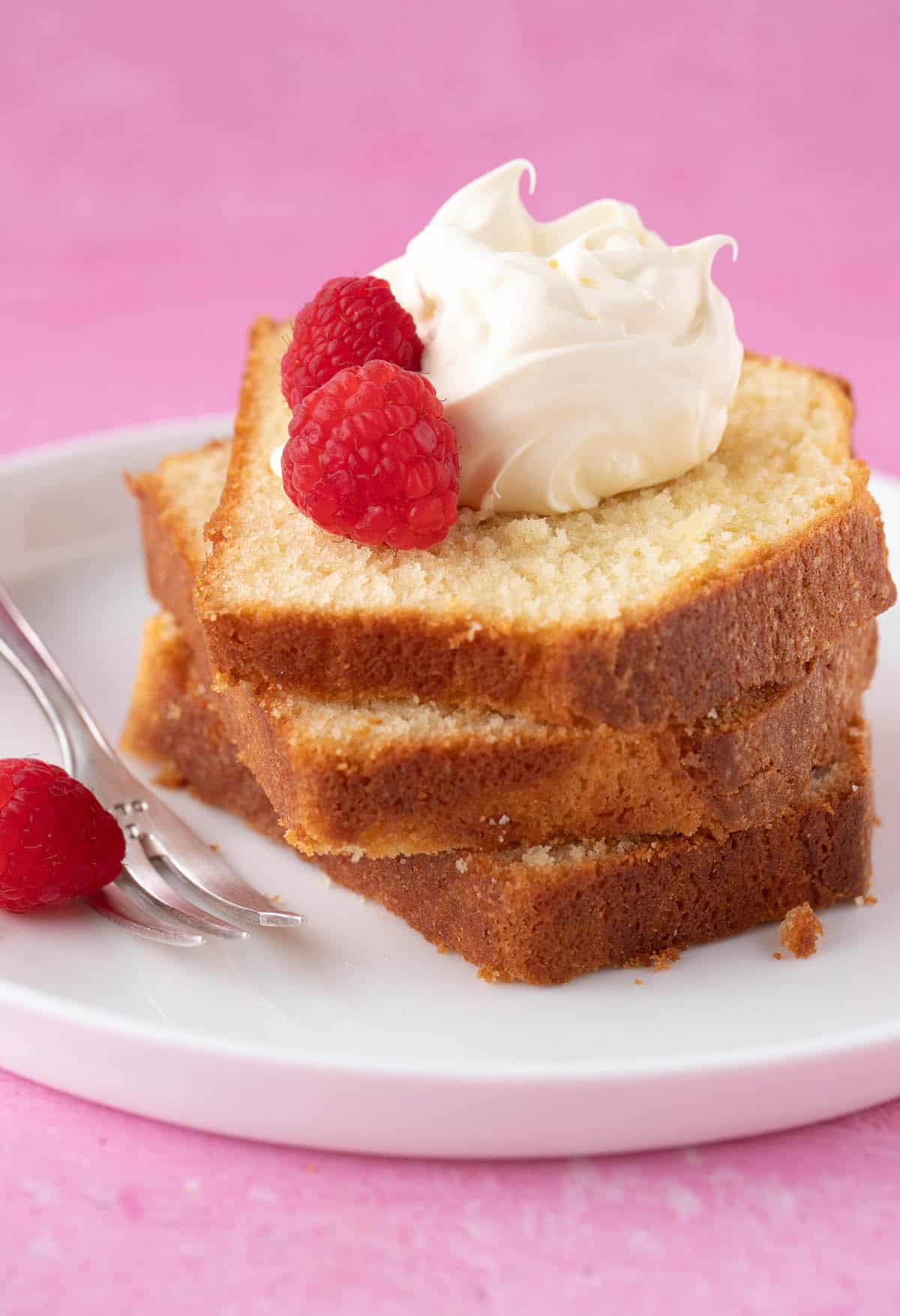 A stack of Pound Cake slices on a white plate, topped with whipped cream and berries