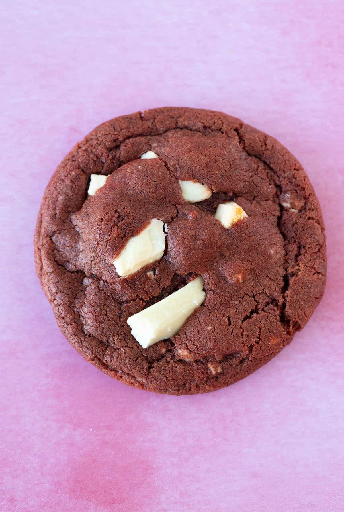 Close up view of a Red Velvet Cookie on a pink background.