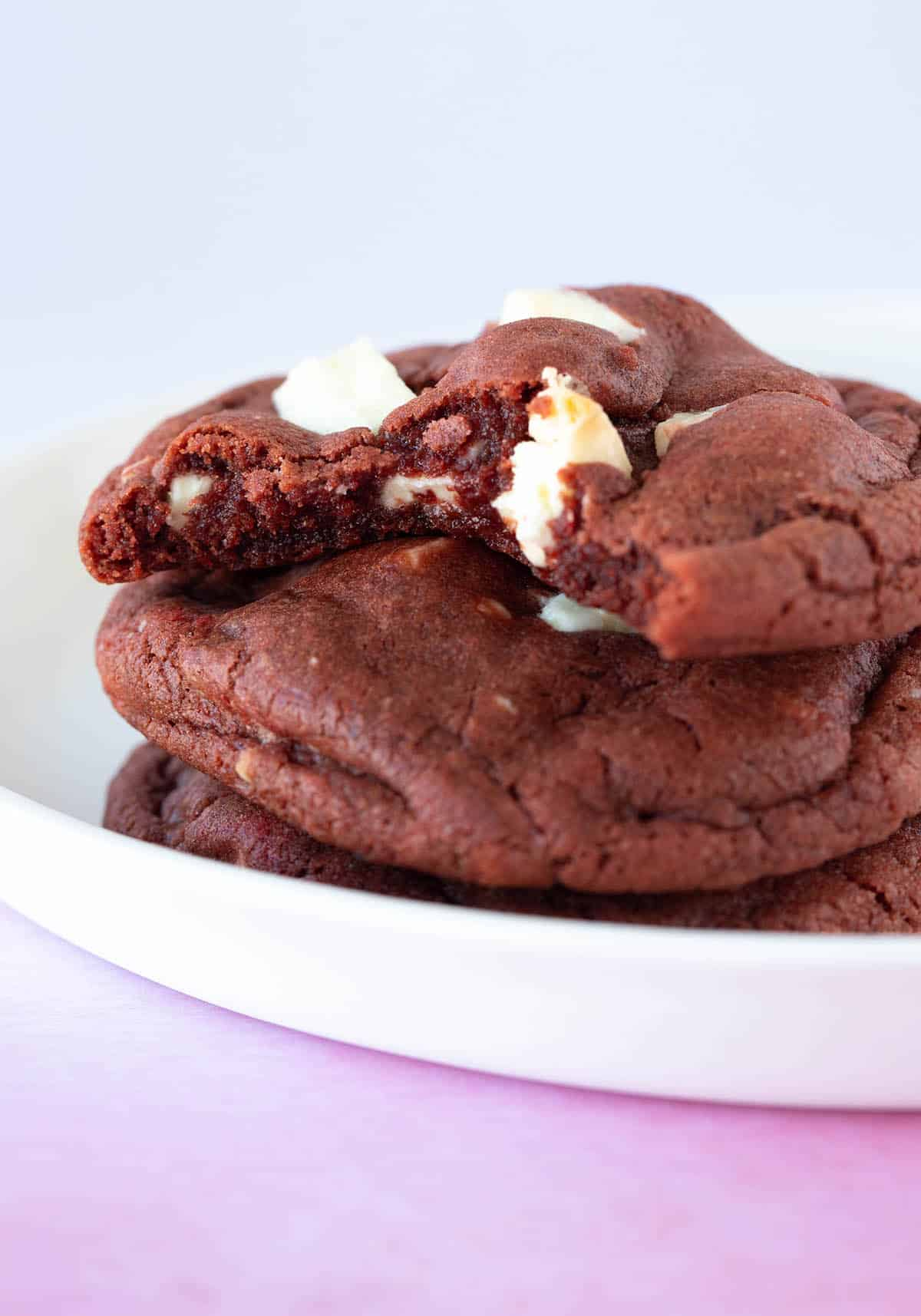 A stack of gooey Red Velvet Cookies with a bite taken out of it.