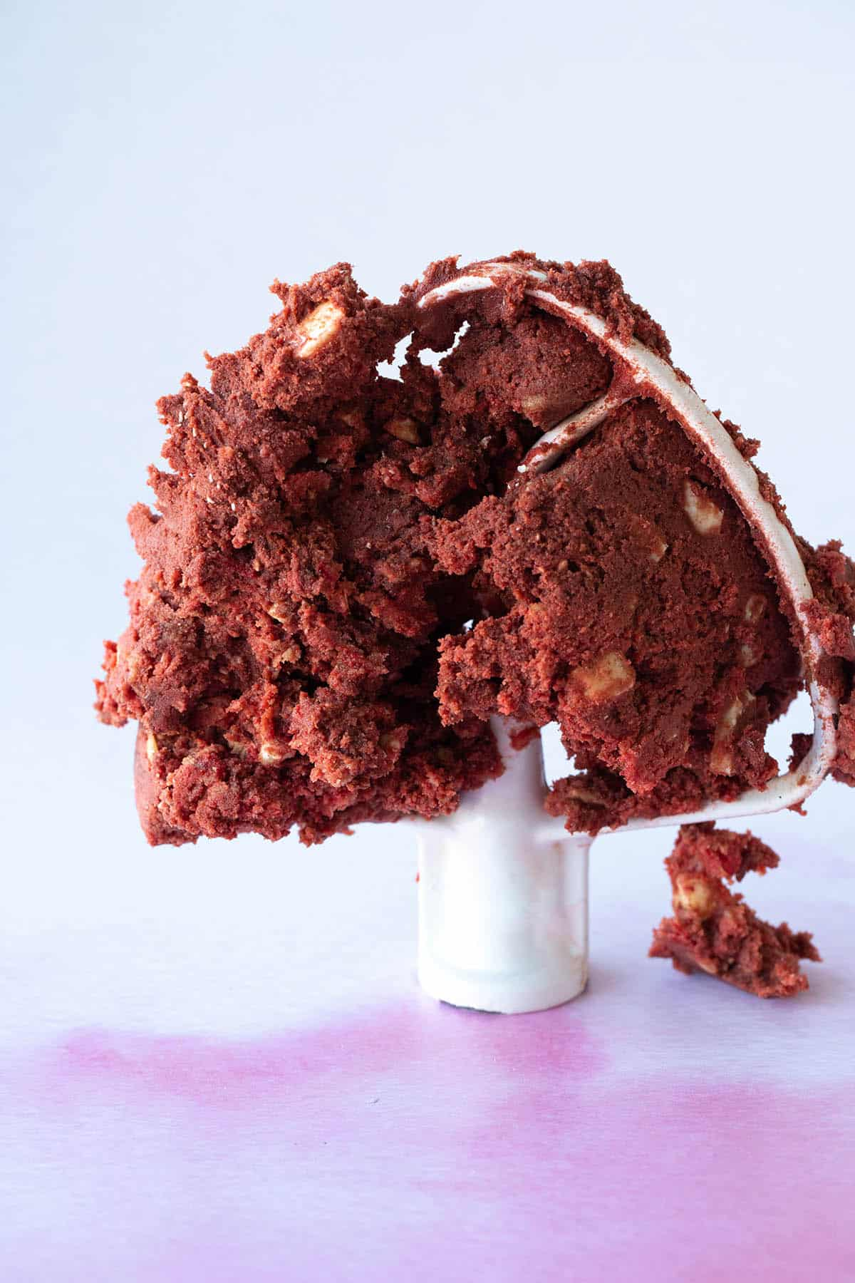 A kitchen aid beater covered in red velvet cookie dough.
