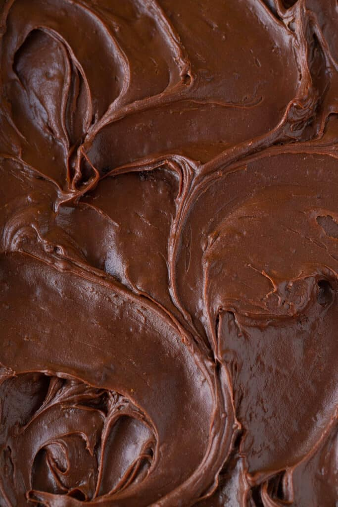 A close up of a chocolate ganache frosting