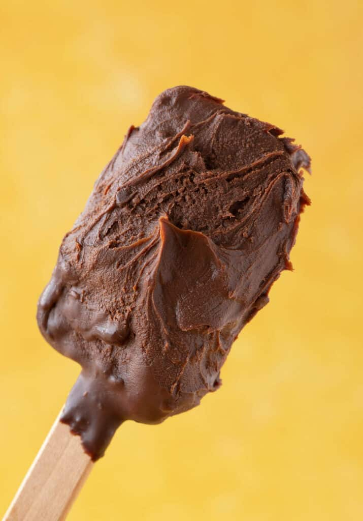 A spatula covered in chocolate ganache frosting