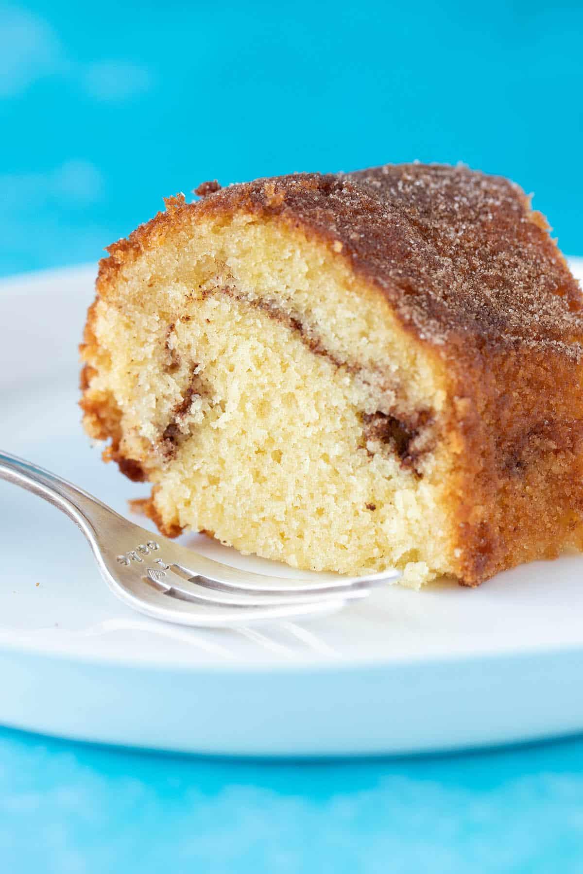 A big slice of cinnamon swirl cake covered in cinnamon sugar