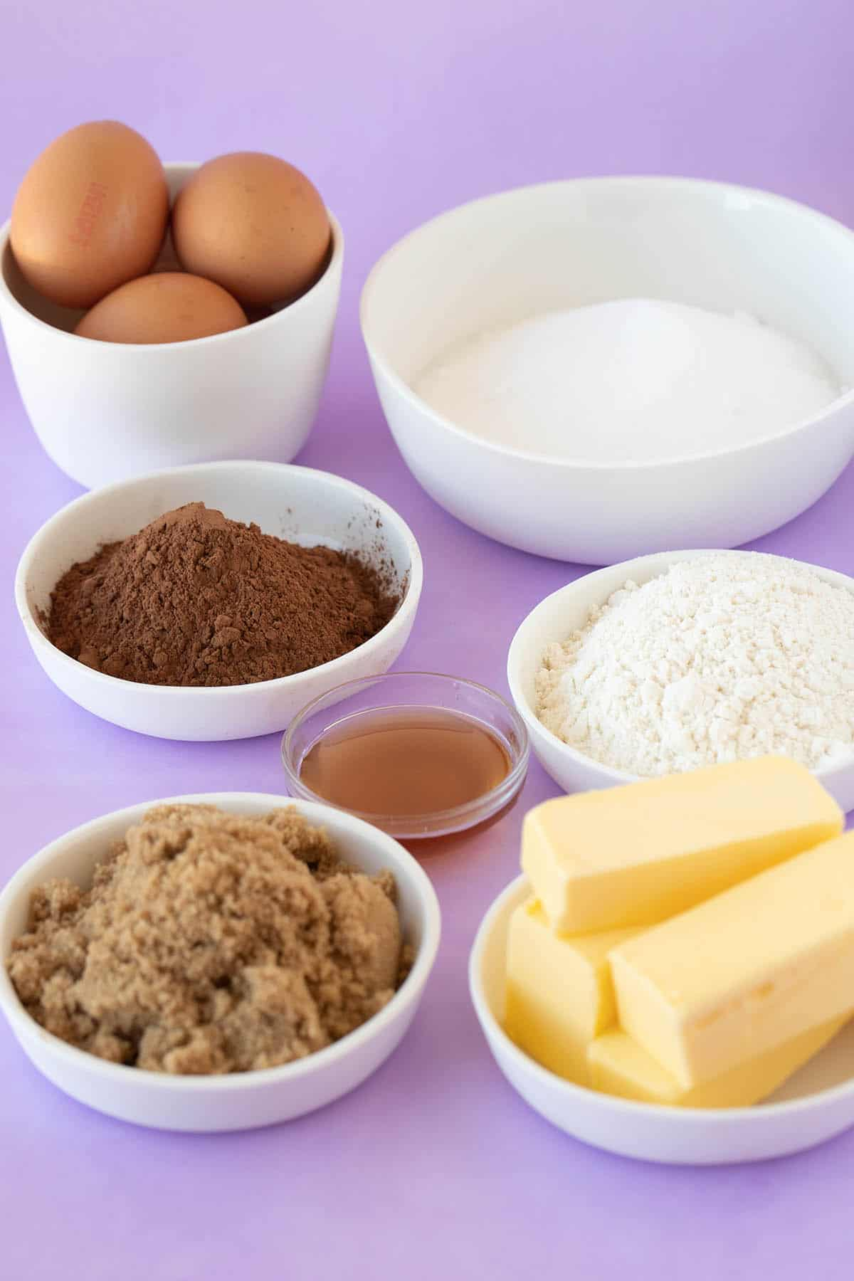 The ingredients for Cocoa Brownies laid out on a purple background